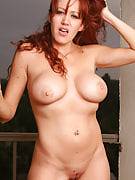 Busty redheaded MILF spreads comfortable in the balcony